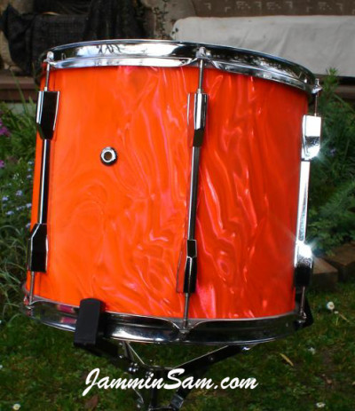 Photo of Brynley Rossiter's drum set with Neon Orange Satin drum wrap (3)